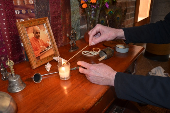 Ken McRae lights a votive on the altar in his alleyCat studio Thursday, March 21. Photo by me.